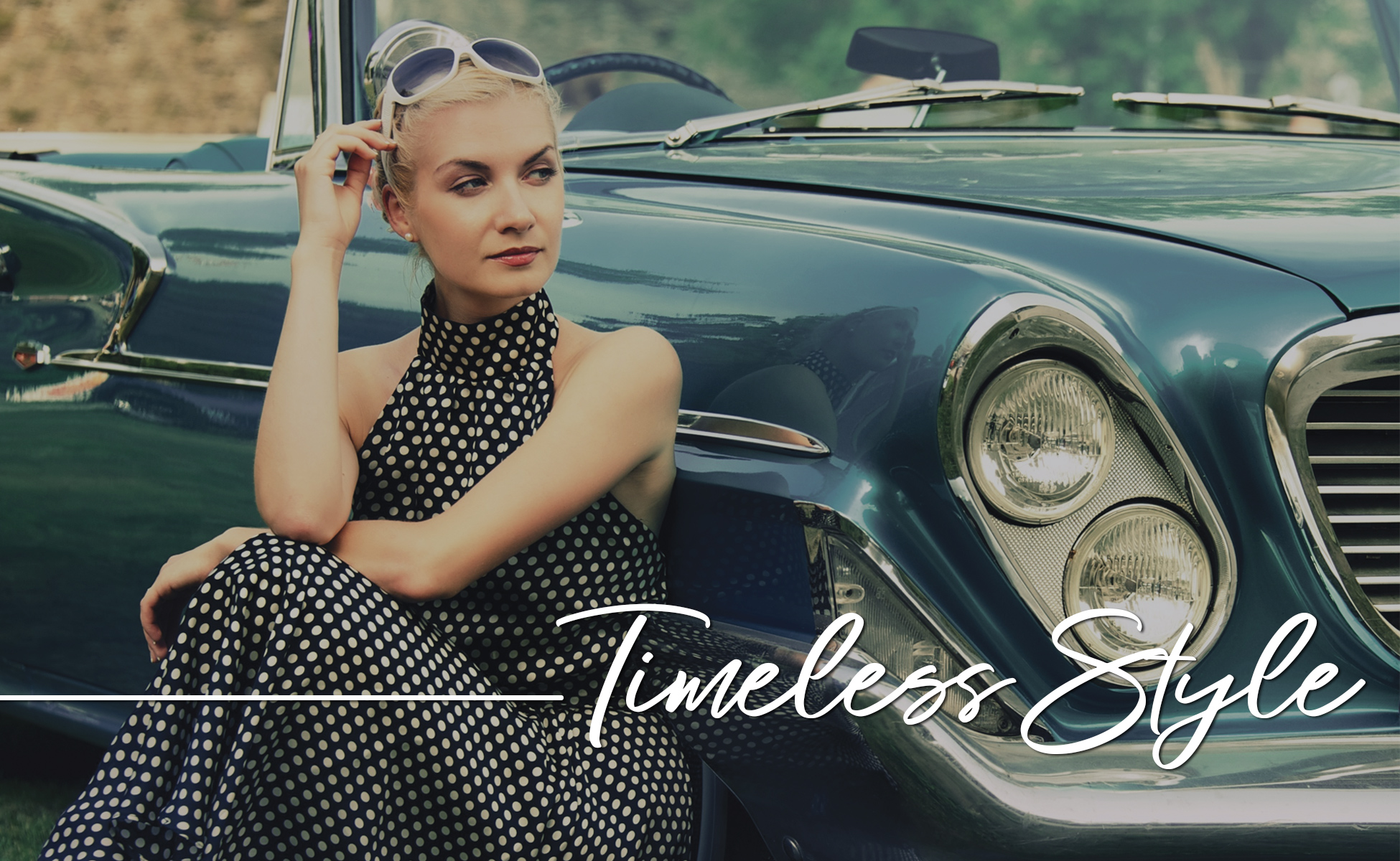 Blue tinted 1950's car with blonde woman wearing sunglasses and polkadot dress leaning against it. Type: Timeless Style