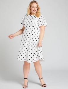 Woman wearing white dress with black polka dots